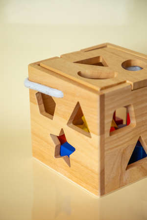 Cute wooden handmade toys for kids on yellow background. Ecological toys concept