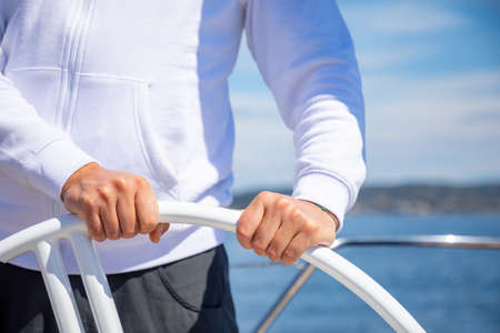 Yachtsman holding the wheel on a sailing boat during yachting, Croatia Banque d'images