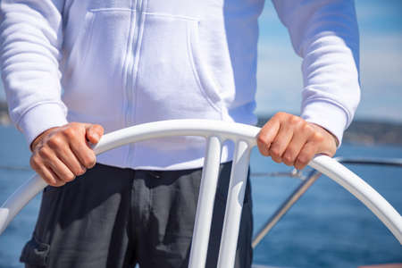 Yachtsman holding the wheel on a sailing boat during yachting, Croatia