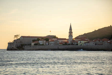 View from water of the old town of Budva city in Montenegro, view from island of St. Nicholas at sunset time