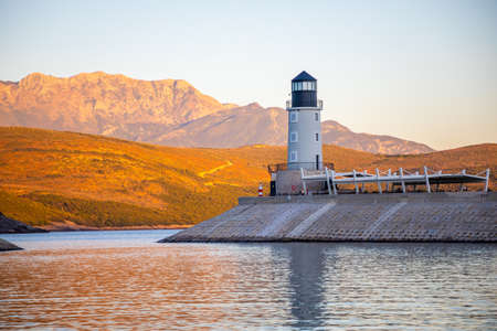 Lustica Bay, Montenegro - October 1, 2021: Lighthouse with restaurant at Lustica Bay in Montenegro at sunset lights