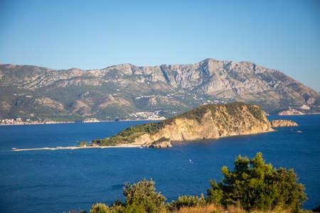 Aerial view of Sveti Nikola or St. Nicolas island is in Budva riviera on mountain background, Montenegro