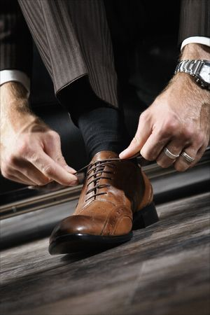 shoes fashion: A businessman is lacing his shoes
