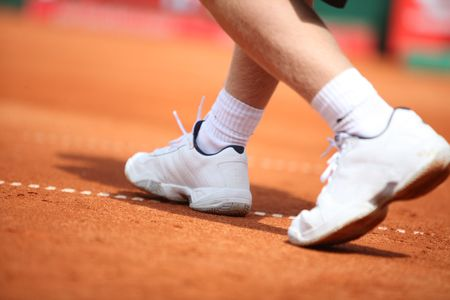 tennis shoe: A man runs over the tennis court with with sport shoes
