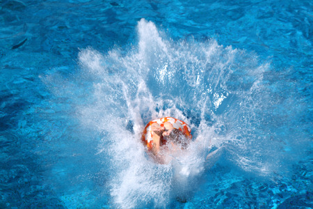 Een jongen springt uit een duik platform in de pool