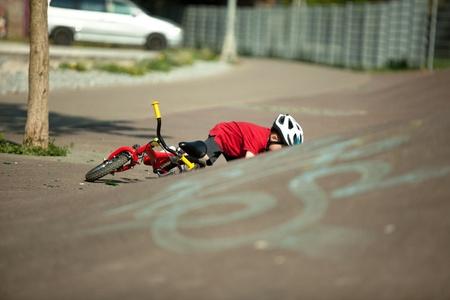 ni�os en bicicleta: Un joven cae de su moto Foto de archivo