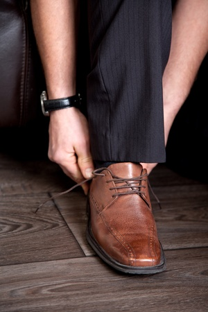 A young business man is lacing his brown leather shoes.