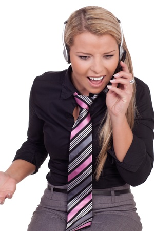 disbelief: Harassed call centre operator reacting in disbelief to a conversation over her headset with a client of the company, studio portrait on white Stock Photo