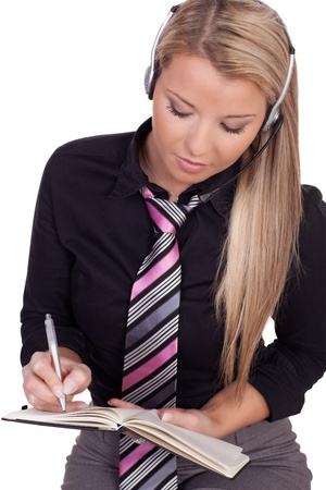 Attractive young blonde personal assistant or receptionist wearing a headset making an appointment for her boss writing with a pen in a diary , closeup half body studio portrait on white Stock Photo