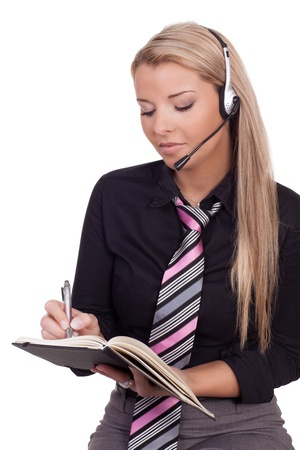 Beautiful blonde female receptionist or personal assistant wearing a headset taking messages or setting appointments for her boss writing in a diary photo