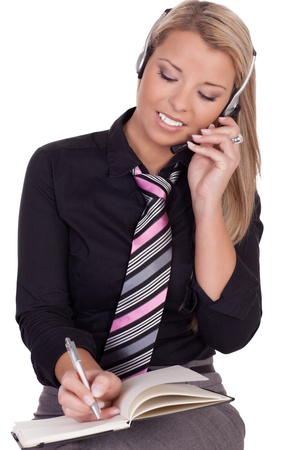 Attractive smiling receptionist or secretary listening to a conversation on her headset making an appointment in a diary for her boss, studio half body portrait isolated on white Stock Photo - 17862081