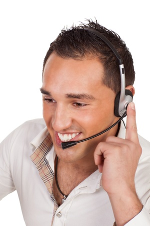 he is public: Friendly male receptionist or call centre operator listening carefully to a call on his headset as he deals with support and public relations for the company
