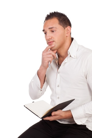 Closeup studio portrait of a handsome young man sitting thinking deeply with a diary or notebook on his lap isolated on white photo