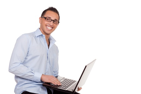 shirtsleeves: Enthusiastic businessman using a laptop balanced on his arm as he sits on a stool conceptual of the wireless connectivity and portability of the computer as a business tool isolated on white Stock Photo