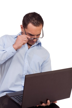 handholding: Man battling to read his laptop screen lowering his glasses by the frame so that he can see better due to the short focal length as he is handholding the computer Stock Photo