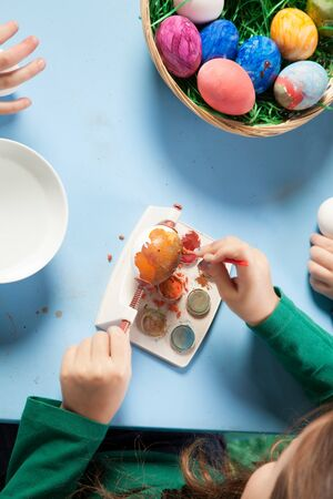 Overhead view of the hands of a child seated at a table painting colourful Easter eggs with a basket full of completed ones alongside Stock Photo - 18097429