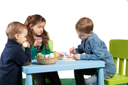 sit around: Three young children decorating Easter eggs sit around a table with a basket of colourful painted eggs between them while a young boy concentrates on completing another