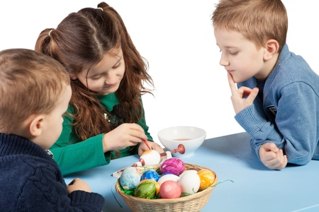 sit around: Three young children, a sister and two brothers, sit around a table painting Easter eggs with a bowl of colourful completed decorated eggs in the foreground