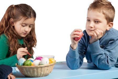 Petite fille peinture des oeufs de Pâques regardé par son frère qui est fièrement tenant un de ses oeufs finis à la main Banque d'images - 18123249