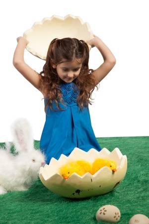 Easter them with young girl holding top egg shape over her head looking into lower half with toy chicks inside  photo