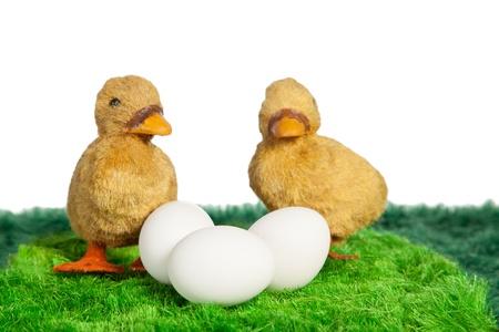 pasto sintetico: Primer plano de dos polluelos de juguete de color amarillo con tres huevos sobre c�sped sint�tico
