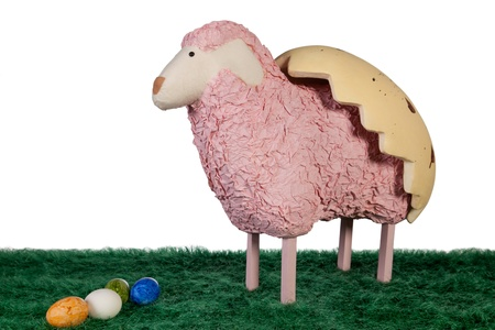 Pink craft made lamb with coloured eggs and half egg shape on it photo