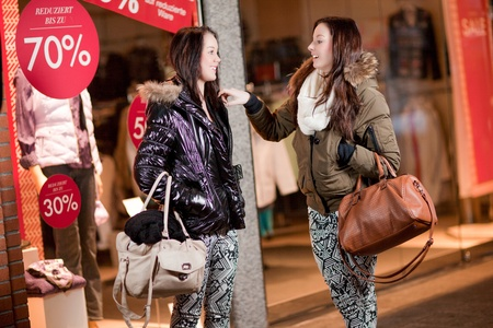 Two laughing fashionable female friends chatting outside a store window in their warm winter clothing Stock Photo - 18353431