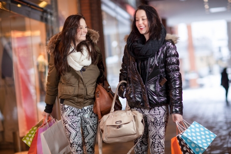 Two beautiful young women friends out shopping together in a mall with their hands full of colourful carrier bags Stock Photo - 18353425