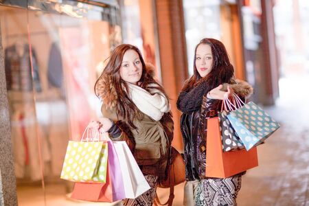 Two beautiful trendy young woman shoppers posing with all their colourful carrier bags in a mall in front of a store window Stock Photo - 18353430