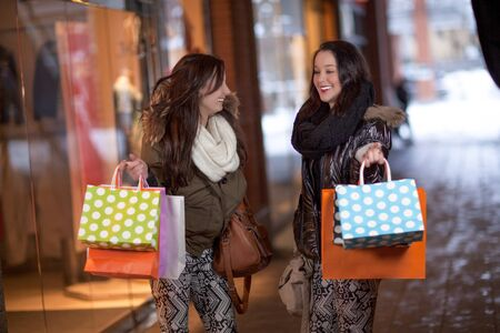 Two happy young women holding colorful shopping bags in front of stores Stock Photo - 18381610