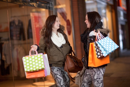 Happy woman shoppers in a mall with their hands full of colourful shopping bags standing chatting and laughing Stock Photo - 18381604