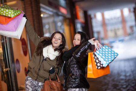 Playful beautiful young female shoppers with lots of purchases standing together in a mall laughing and holding their shopping bags up in the air
