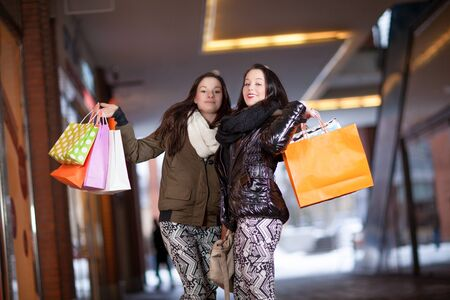 Two stylish beautiful playful female shoppers having fun posing with handfuls of colourful carrier bags with their purchases Stock Photo - 18381603