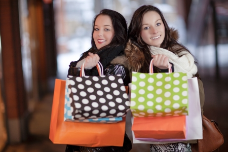 Two middle-aged happy women standing back to back and holding shopping bags Stock Photo - 18381601
