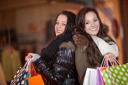 Two beautiful happy female shoppers standing back to back each with a handful of colourful shopping bags from the stores Stock Photo - 18411716