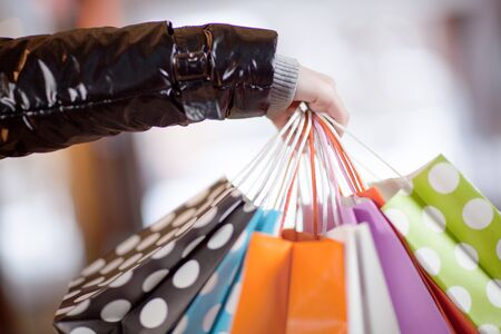 Conceptual cropped view image of the hand of a female shopaholic laden with numerous multicoloured shopping bags full of her purchases Stock Photo