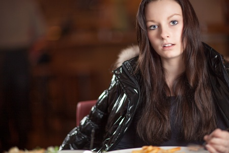 sincere: Candid portrait of an attractive serious sincere young woman sitting at a dining table looking at the camera, with copyspace