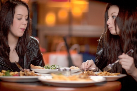 Two attractive women enjoying a meal together sitting at a table in a restaurant, view across the table and food photo