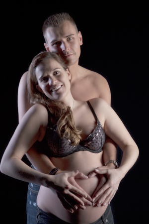encircling: Loving pregnant couple with the husband encircling his wife protectively with his arms and both their hands on her bare belly Stock Photo