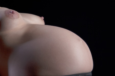 Closeup portrait of the bare breasts and pregnant belly of a woman expecting twins against a dark studio background Stock Photo - 19001356