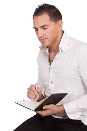 Portrait of man thinking while holding a pen and notebook