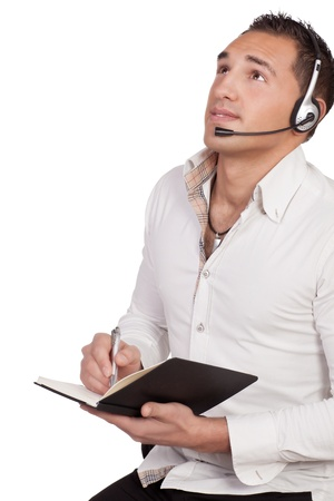 Man wearing a headset staring upwards as he listens to the conversation while taking notes, conceptual of a call centre, help desk, reception or client services Stock Photo - 19114785