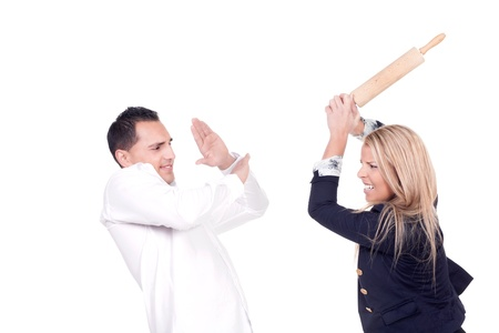 Angry blond woman hitting her partner with a cooking roller in a fight photo
