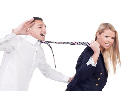 domination: Attractive blonde woman with a disgruntled frowning expression pulling a protesting man along behind her by his tie isolated on white