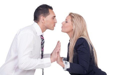 puckered lips: Young married couple making up after a disagreement and preparing to kiss leaning towards each other with their lips puckered isolated on white