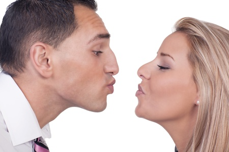 puckered lips: Close cropped portrait of the faces of a young man and woman preparing to kiss leaning towards each other with their lips puckered, isolated on white Stock Photo