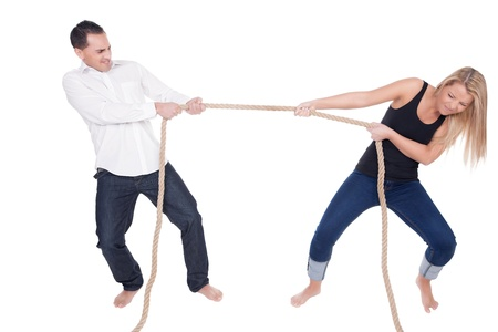 Man and woman having a tug of war each leaning back and straining with the effort of pulling the rope in opposite directions, full body studio portrait on white