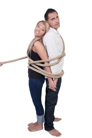 captivity: Barefoot casual young couple bound together by a rope standing back to back, full body studio portrait isolated on white