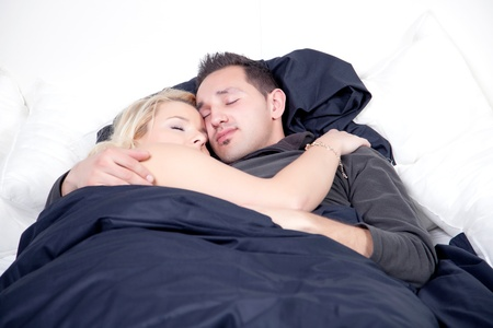 Young couple sleeping peacefully in bed clasped in each others arms with contented serene expressions photo