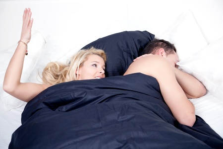 Frustrated woman in bed with her husband raising her hand to slap him as he lies sleeping alongside with his back to her photo